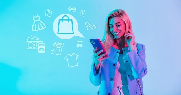 Bella donna sorridente felice in vestiti alla moda che tiene smartphone e che fa shopping online con le icone dello shopping su sfondo blu. la ragazza fa acquisti su internet tramite l'applicazione