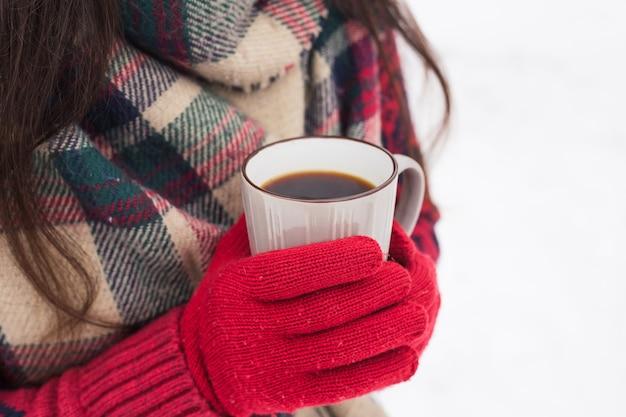 Bella donna sorridente felice con una tazza in inverno sulla strada