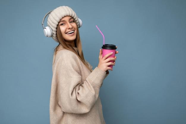 Bella giovane donna bionda sorridente felice che indossa un maglione invernale beige e cappello isolato
