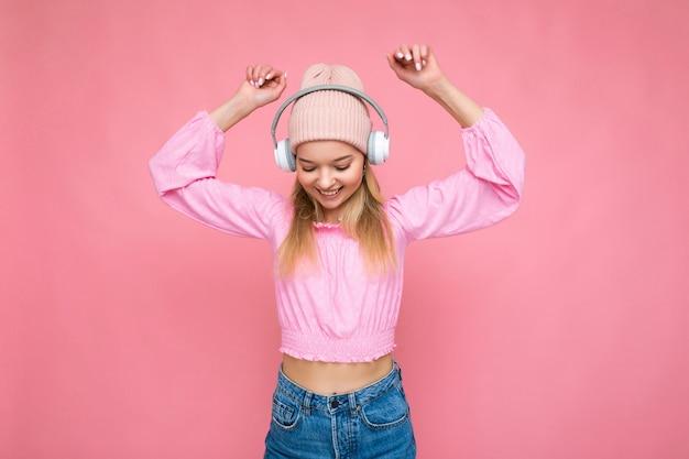 Bella giovane donna bionda sorridente felice che indossa camicetta rosa e cappello rosa isolato su rosa over