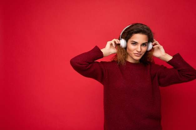 Bella giovane donna riccia bruna sorridente felice che indossa un maglione rosso scuro