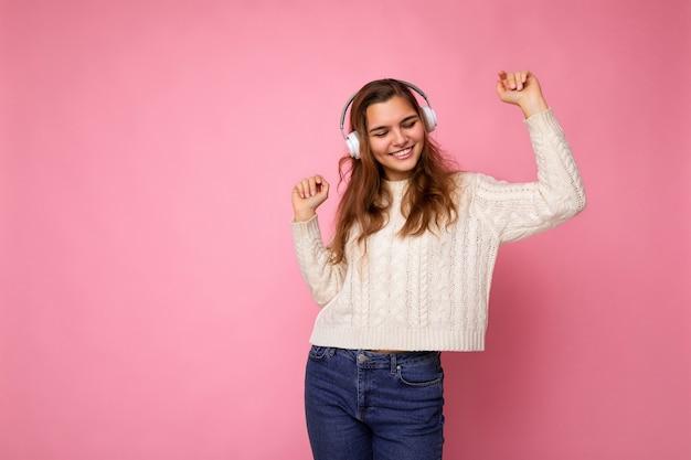 Bella sorridente giovane donna riccia bruna che indossa un maglione bianco isolato su sfondo rosa