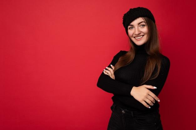 Bella giovane donna bruna sorridente felice isolata su red