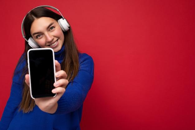 Bella giovane donna sorridente felice che porta vestito casuale alla moda isolato sulla parete del fondo