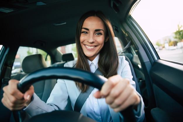 Bella donna d'affari di successo felice sta guidando una nuova auto moderna di buon umore. ritratto carino pilota femminile che guida l'auto con cintura di sicurezza