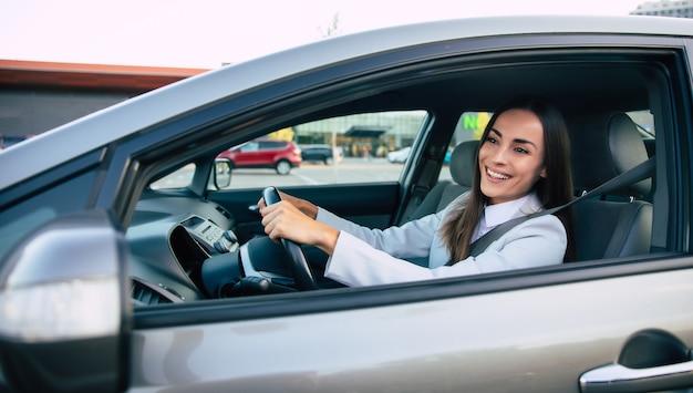 Bella donna d'affari di successo felice sta guidando una nuova auto moderna di buon umore.