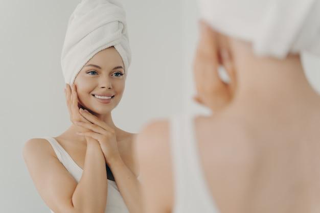 Bella donna felice dopo aver applicato il trucco guardandosi allo specchio e sorridendo mentre si trovava in bagno, donna piuttosto giovane con un asciugamano bianco sulla testa che tocca delicatamente il viso. concetto di bellezza e cura della pelle