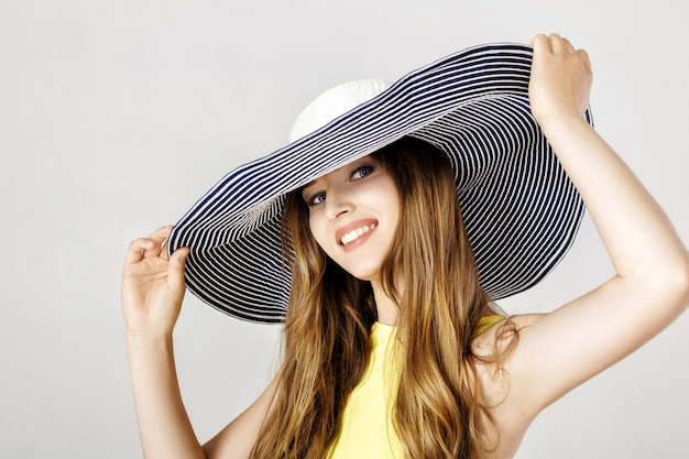 Bella donna felice con un cappello estivo blu