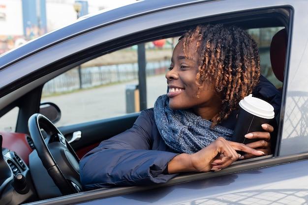 La bella e felice donna in macchina