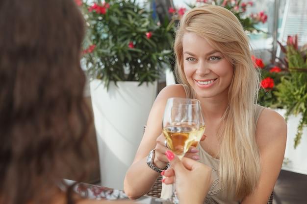 Bella donna felice tintinnio di bicchieri con il suo amico, godendo di bere vino al bar