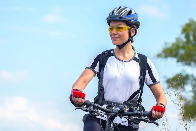 Bella e felice donna ciclista con una bicicletta sulla natura