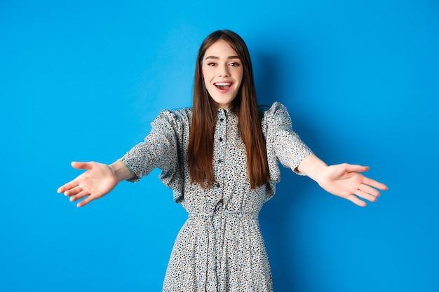 Bella donna felice in abito allunga le mani in un caloroso benvenuto, sorridendo e salutandoti, invitando gli ospiti, in piedi sul blu.
