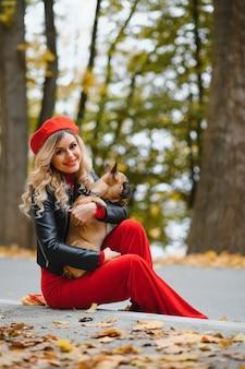 Bella e donna felice che si diverte nel parco camminando con il suo adorabile bulldog francese.