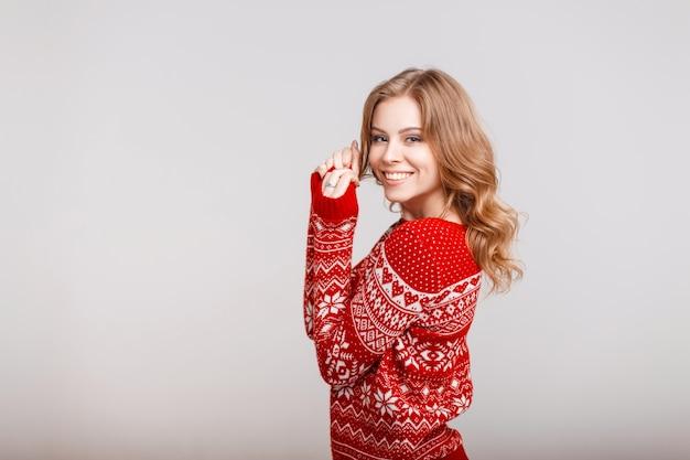 Bella donna felice in un maglione rosso vintage di moda su uno sfondo grigio al chiuso
