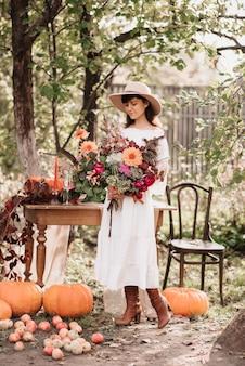 Una bella donna felice tiene in mano un mazzo di fiori ed erbe aromatiche. umore autunnale