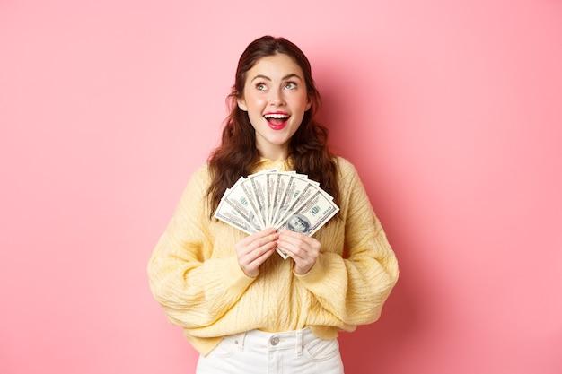 Bella donna felice che sembra sognante da parte, con in mano banconote da un dollaro, pensando di fare shopping o sprecare soldi, in piedi su sfondo rosa