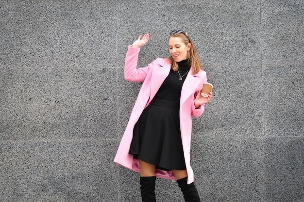 Bella e felice donna in cappotto rosa e stivali al ginocchio in piedi con la tazza di caffè e in posa sulla fotocamera sul fondo della parete di granito