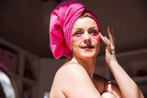 Una donna bella e felice con le toppe rosa sotto gli occhi posa in un bagno soleggiato la donna distoglie lo sguardo e tocca le toppe con la mano