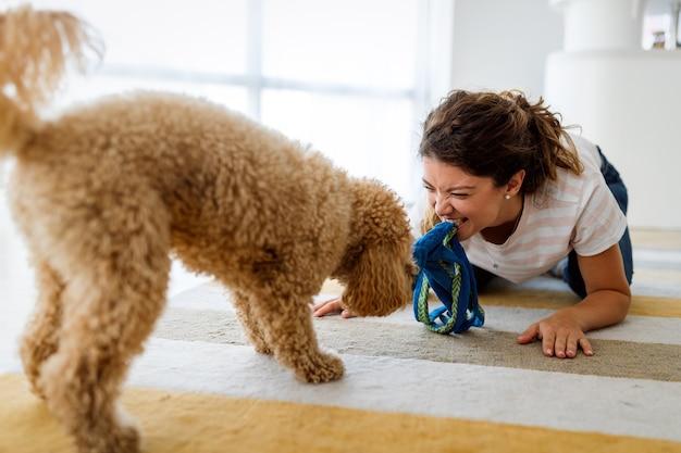 Bella donna felice che gioca con un bel cane carino a casa. persone, cane, concetto di amore
