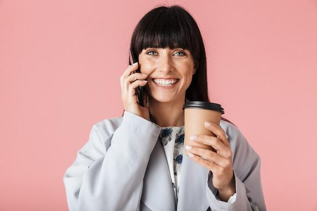 Una bella donna felice in posa isolata sul muro rosa chiaro che parla al telefono cellulare tenendo il caffè.