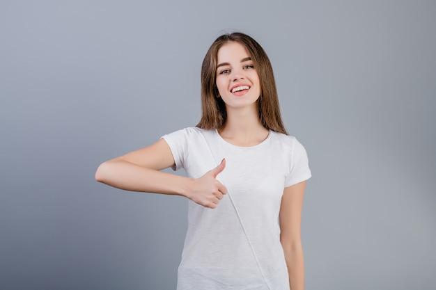 Bella donna felice che mostra i pollici in su isolati sopra grey