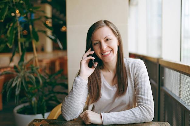 Bella donna felice seduta da sola vicino alla grande finestra in caffetteria, rilassante nel ristorante durante il tempo libero. giovane donna che parla con il telefono cellulare, riposa nella caffetteria. concetto di stile di vita