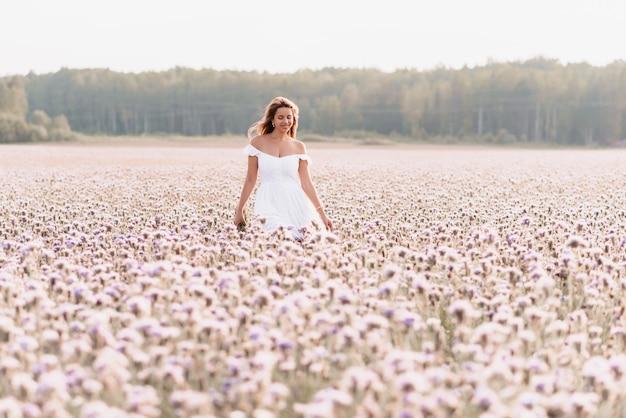 Bella donna felice in un abito bianco in un campo di fiori in estate nella natura