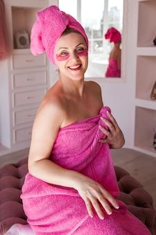 Una donna bella e felice con un corpo e capelli avvolti in un asciugamano rosa e con macchie rosa sotto gli occhi sta posando in bagno.