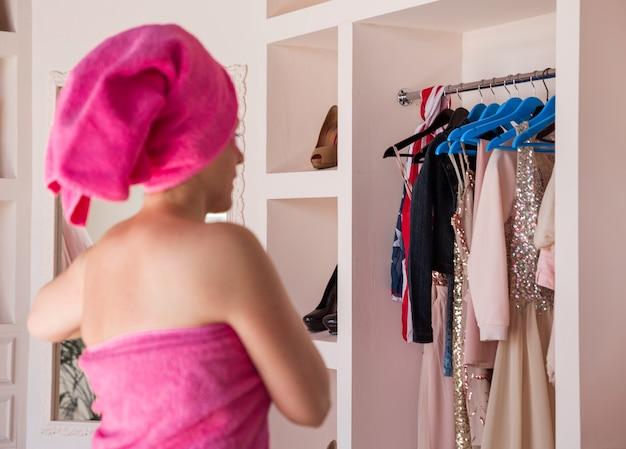 Una donna bella e felice con un corpo e capelli avvolti in un asciugamano rosa e con macchie rosa sotto gli occhi sta posando in camera da letto