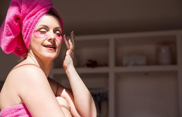 Una donna bella e felice con un corpo e capelli avvolti in un asciugamano rosa e con macchie rosa sotto gli occhi
