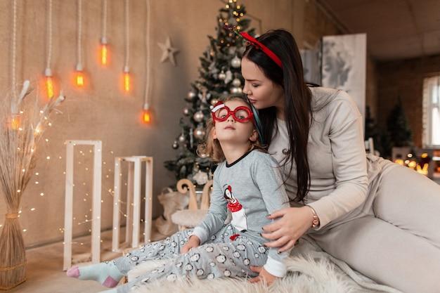Bella donna felice con una bambina in pigiama alla moda è seduta sul letto sullo sfondo di un albero di natale, decorazioni e luci. vacanze invernali in famiglia a casa