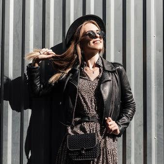 Bella donna felice con un sorriso in abiti autunnali alla moda con polsino, vestito, giacca di pelle e occhiali da sole con una borsa vicino a una parete di metallo