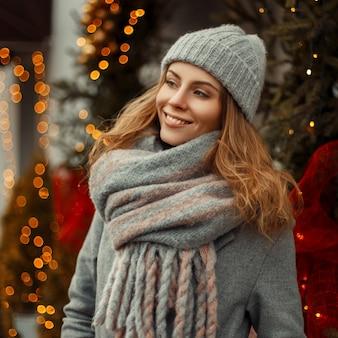 Bella donna felice con un sorriso in un cappello lavorato a maglia alla moda cappotto grigio e sciarpa vicino a un albero di natale e luci in città
