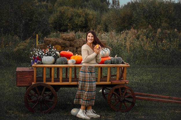 Bella donna felice con un carretto di legno con zucche colorate