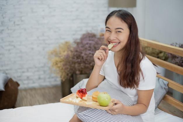 Bella donna felice di yong che mangia prima colazione con frutta e dolce sul letto