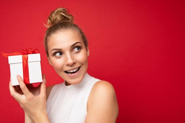 Bella giovane donna bionda felice isolata sopra la parete variopinta del fondo che porta casuale alla moda