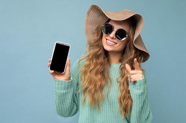 Bella giovane donna bionda felice che indossa occhiali da sole e cappello estivo isolato su sfondo blu