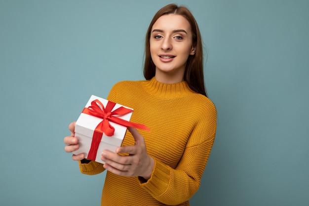 Bella giovane donna bruna felice isolata su una parete di fondo colorata che indossa abiti casual eleganti che tengono una scatola regalo e guardano la telecamera