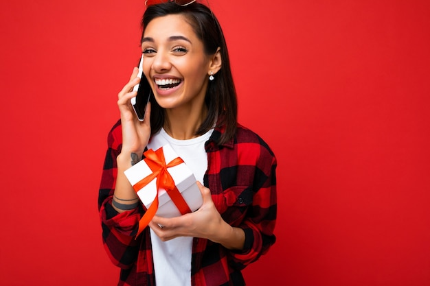 Bella giovane donna castana felice isolata sopra la parete variopinta del fondo che indossa vestiti casuali alla moda che tengono il contenitore di regalo e che guarda al lato.
