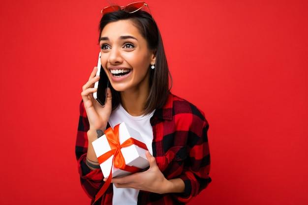 Bella giovane donna castana felice isolata sopra la parete variopinta della parete che porta vestiti casuali alla moda che tengono il contenitore di regalo e che osserva al lato.
