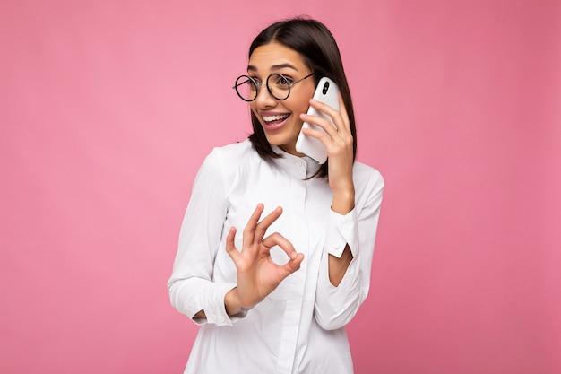 Bella giovane donna bruna felice che indossa una camicetta bianca e occhiali ottici in piedi isolata sopra il rosa