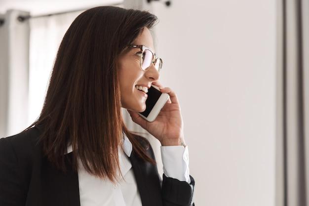 Bella giovane donna d'affari felice in abiti da cerimonia al chiuso a casa parlando al telefono cellulare.