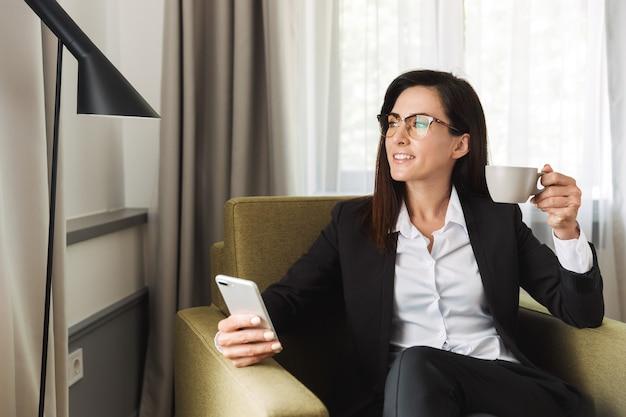 Bella giovane donna d'affari felice in abiti da cerimonia al chiuso a casa usando il telefono cellulare bevendo caffè.