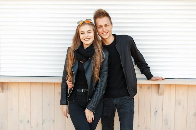 Belle giovani coppie felici che sorridono in vestiti alla moda alla moda vicino al muro bianco