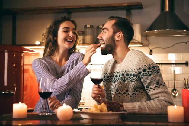Belle giovani coppie felici che trascorrono insieme una serata romantica a casa, bevendo vino rosso, alimentando