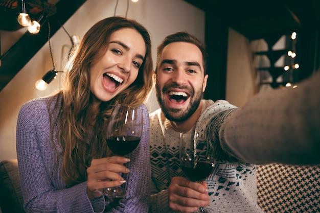 Belle giovani coppie felici che trascorrono insieme una serata romantica a casa, bevendo vino rosso, prendendo un selfie