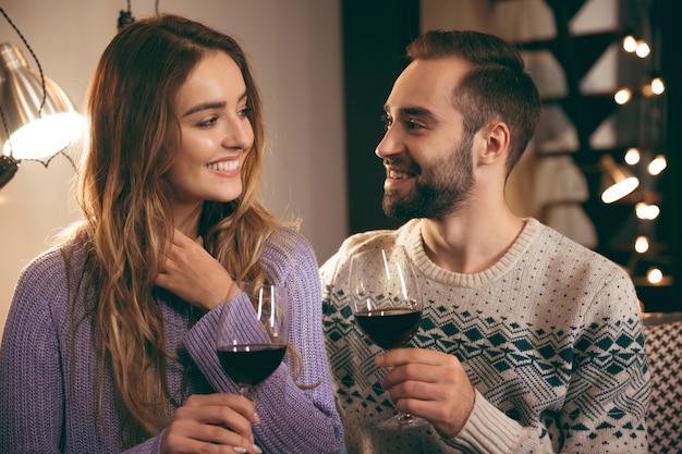 Bella giovane coppia felice trascorrere una serata romantica insieme a casa, bere vino rosso, tostare