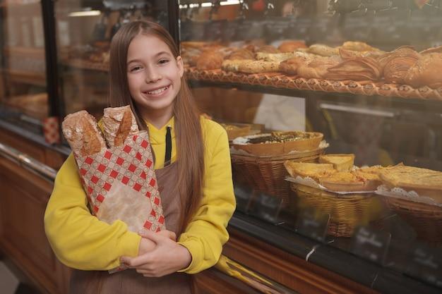 Bella ragazza felice che indossa il grembiule, tenendo il pane fresco, aiutando i suoi genitori al forno di famiglia
