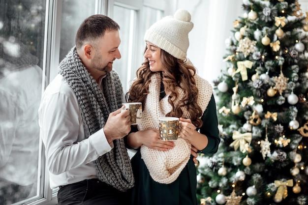 Bella e giovane coppia sposata felice vicino alla finestra