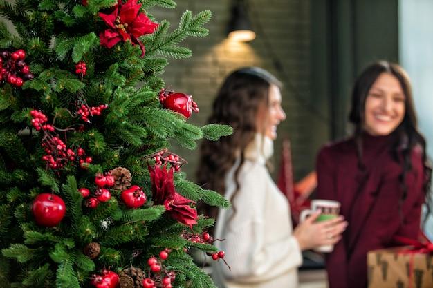 Belle due giovani donne felici in cucina sullo sfondo delle decorazioni natalizie